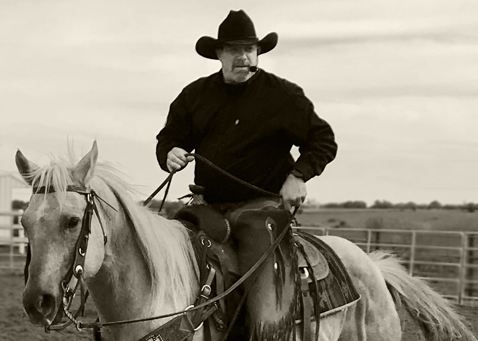 Sepia toned photo of cowboy on a palomino giving riding instructions.