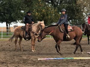 Two riding students on their horses receiving instruction from their teacher.