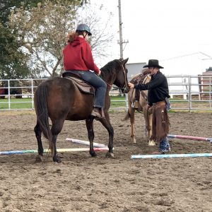 Riding instructor working with a young girl on her horse