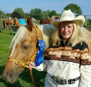 Blonde woman with her palomino mare wearing blue ribbons she won in a horse show.