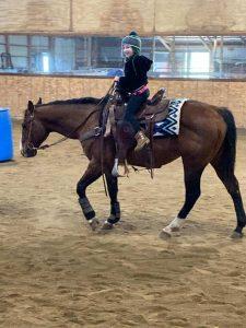 smiling little girl getting horseback riding lessons