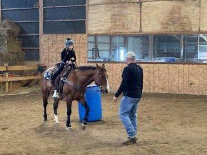 little girl getting horseback riding lessons