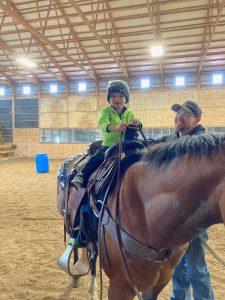 three-year-old boy sitting on a horse