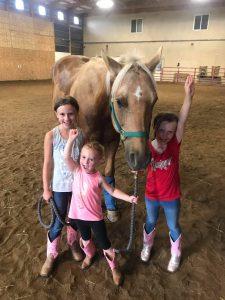 Three little girls standing with palomino horse.