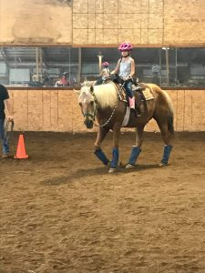 Little girl getting riding lessons