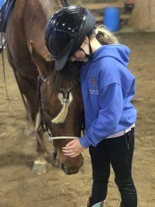 Little girl pets a horse