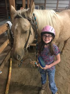 Little girl standing next to a palomino horse.